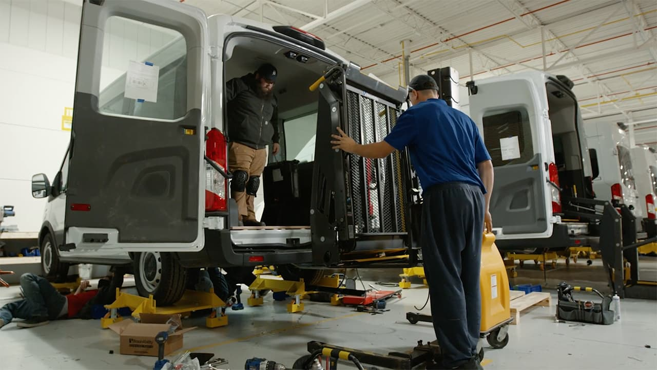 Employees assembling additional components to van