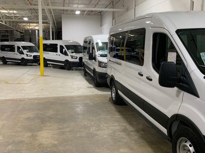 A line of transit vans inside warehouse